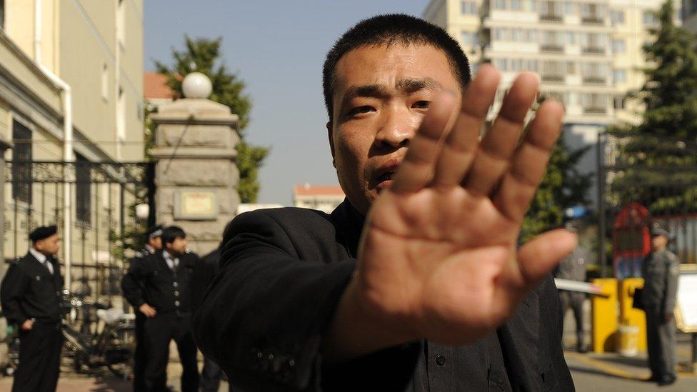 Un guarda de seguridad prohíbe tomar fotografías a la entrada de la casa de la viuda del Nobel de la Paz, Liu Xiaobo, en Pekín.