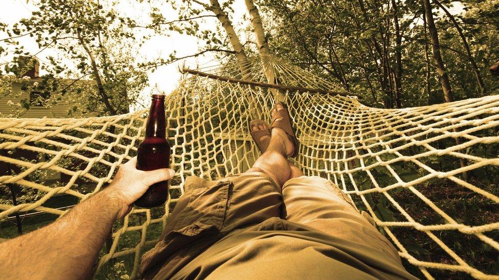 Hombre en hamaca con cerveza