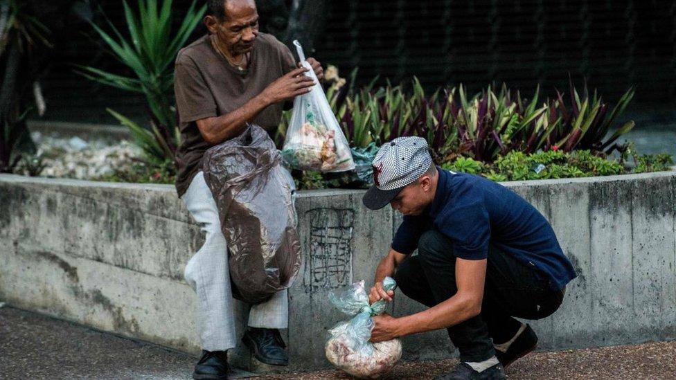 Dos hombres buscan comida en bolsas de basura en Caracas.