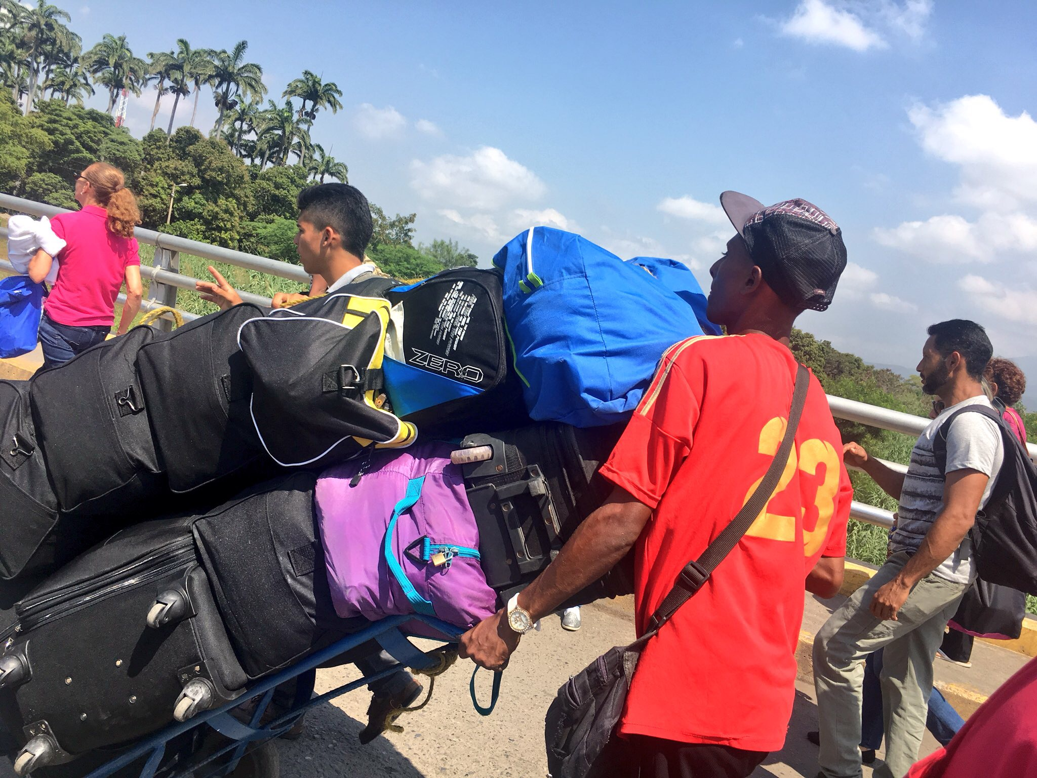 Personas cruzando la frontera con sus maletas