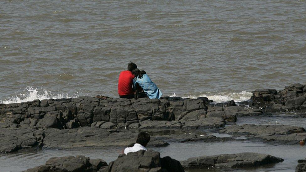 Una pareja se abraza en el malecón de la ciudad india de Bombay.