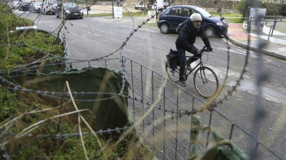 صورة قبرصي يركب دراجة هوائية قرب أسلاك شائكة
