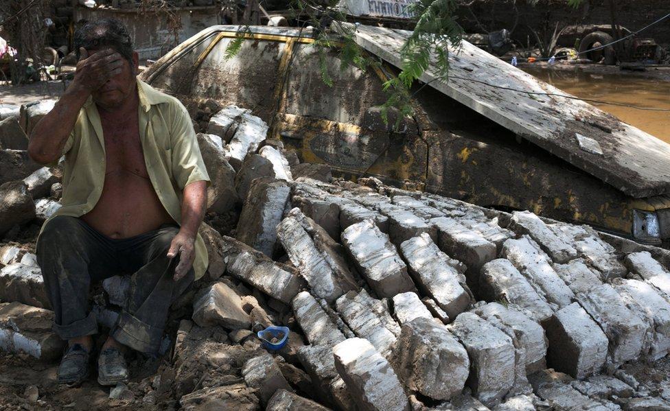 Persona se lamenta sobre los escombros de su casa.