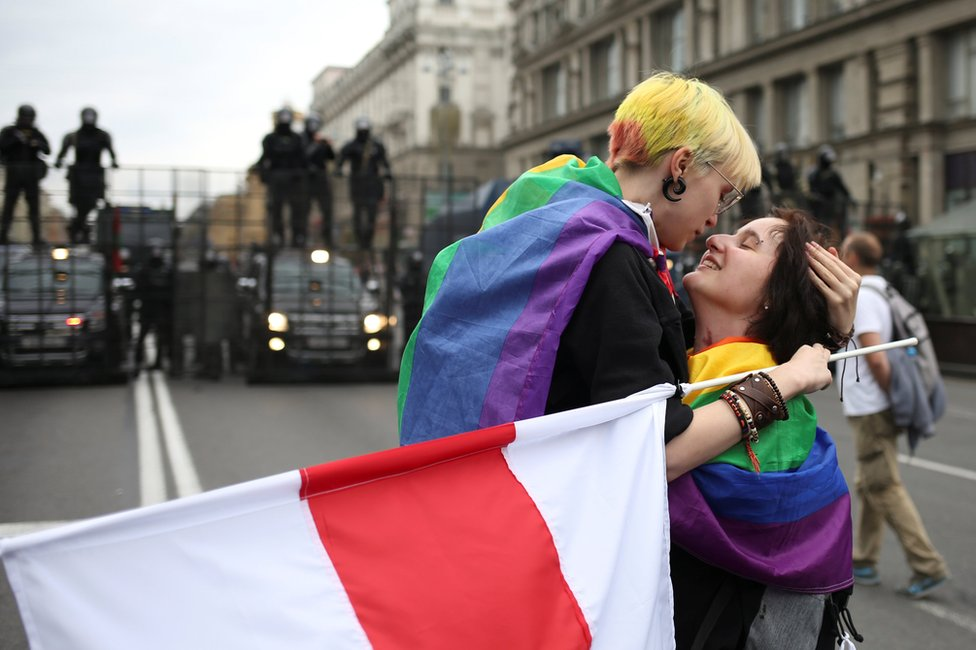 Participants with rainbow-themed flags, representing the LGBT symbol, embrace near barriers erected by Belarusian law enforcement officers during an opposition rally to protest against police brutality and to reject the presidential election results in Minsk, Belarus, 6 September