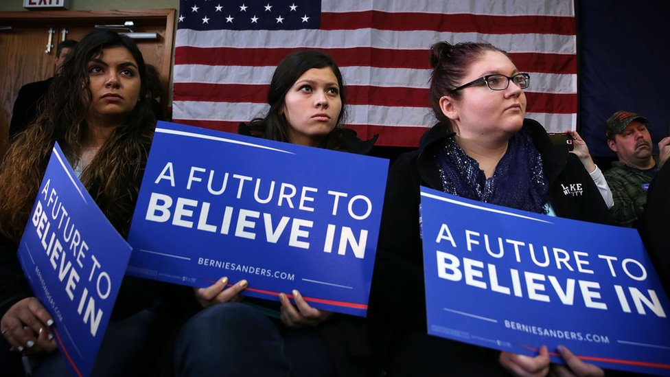 """Bernie Sanders supporters holding placards reading """"A future to believe in"""""""