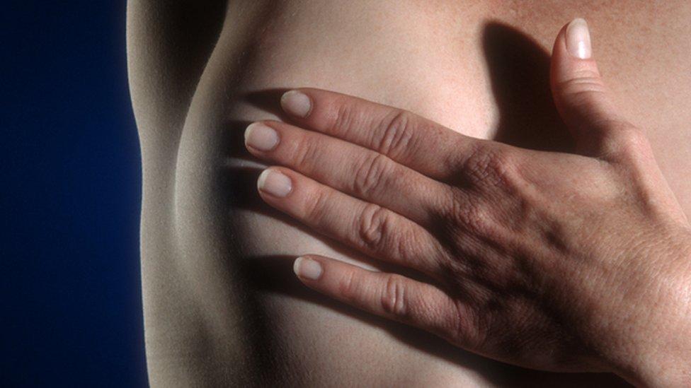 Mujer examinándose el pecho