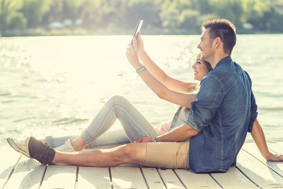 Pareja sentada en un muelle tomándose una foto con un celular.