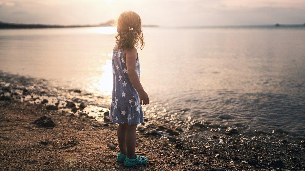 Una niña mira hacia el mar