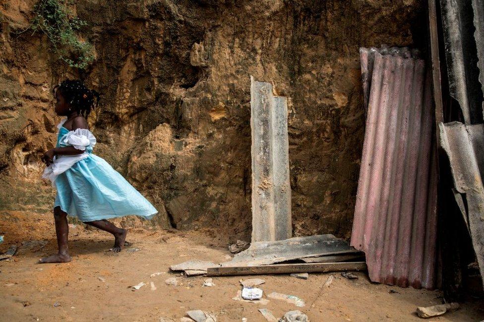 فتاة تمشي قرب بقايا منازل دمرت بسبب انهيار طيني في حي فقير بالكونغو الديمقراطية