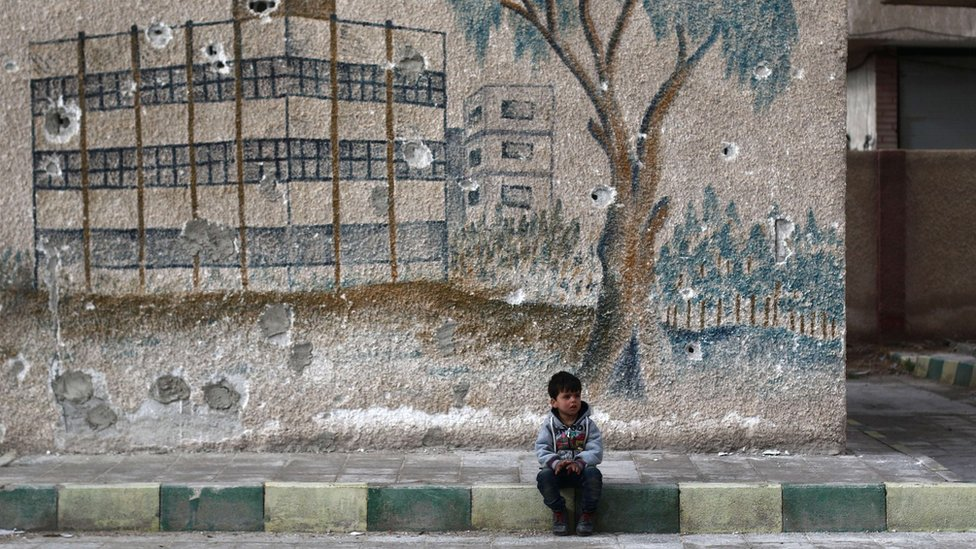 A Syrian child sits in front of a mural covered in bullet holes on the wall of a former school in the rebel-held eastern Ghouta, on the outskirts of the Syrian capital Damascus, on January 5, 2016.