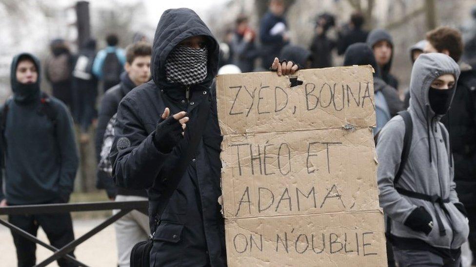 شاب يحملة لافتة احتجاجية خلال المسيرة في باريس