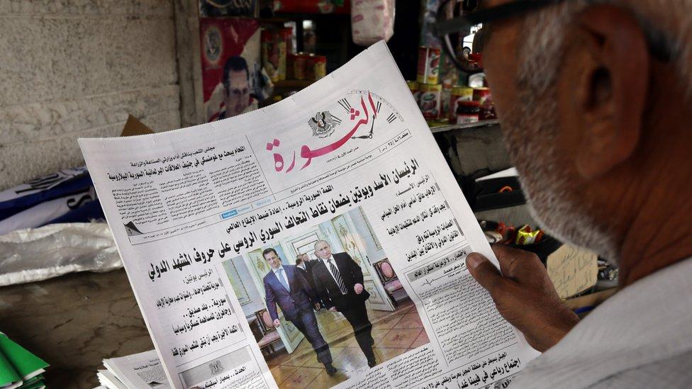 Man reading Syrian newspaper