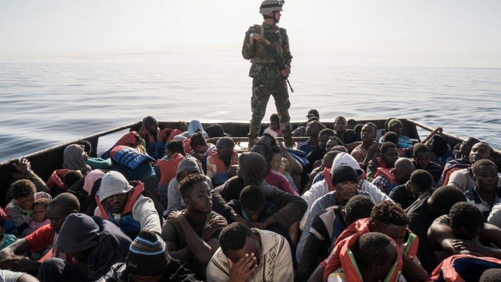 جندي ليبي يجرس قاربا مكتظا باللاجئين والمهاجرين