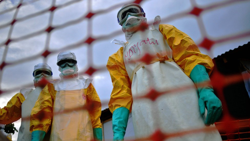 Personas con trajes para evitar enfermedades.
