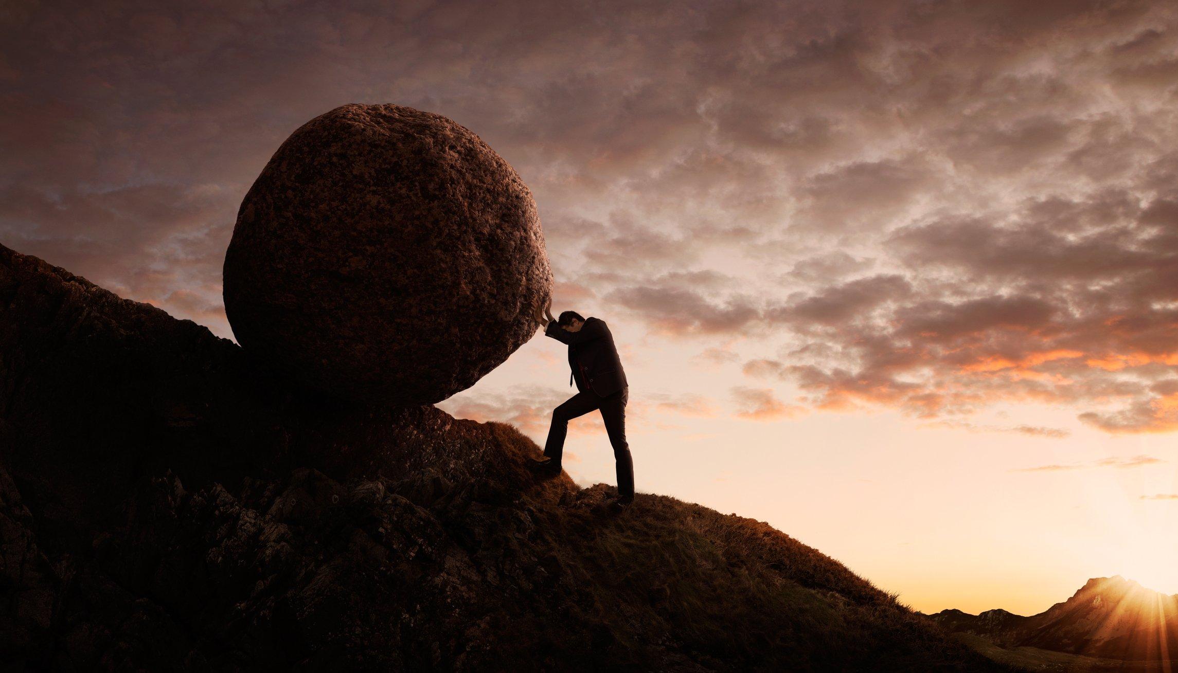 Un hombre empujando una piedra