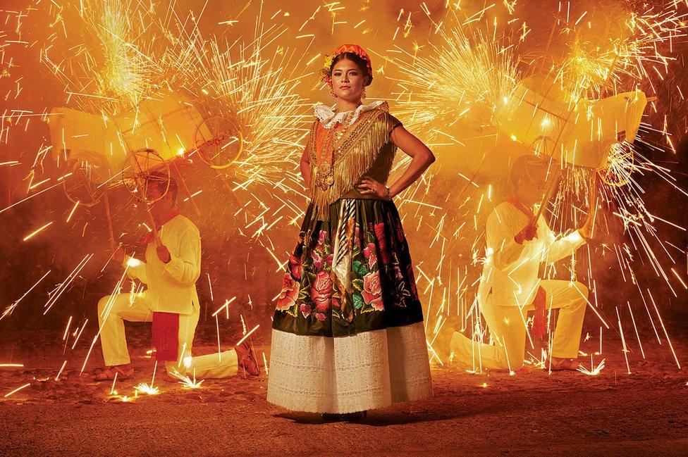 Una mujer posa durante una festividad con fuegos pirotécnicos.