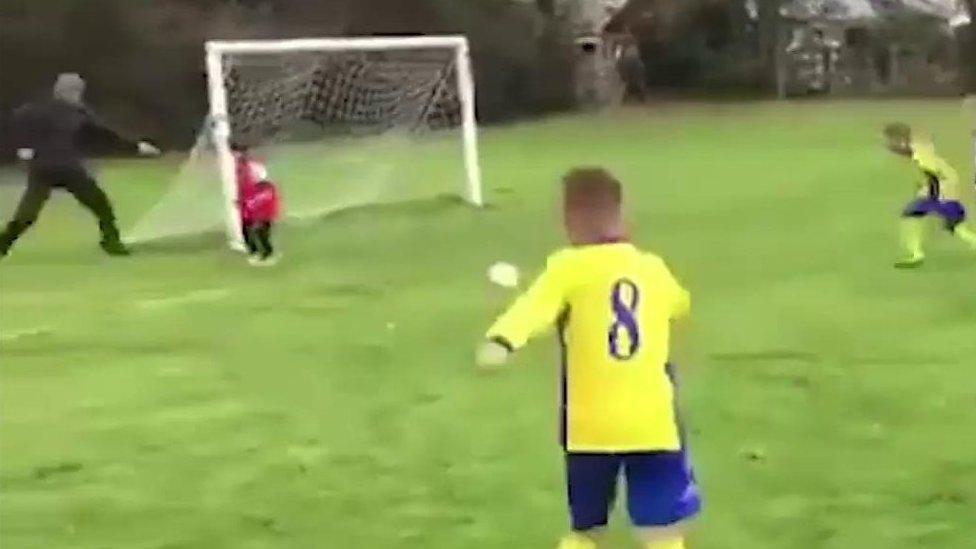 El momento en que un padre empuja a su hijo para que detenga un gol en un partid ...