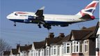A British Airways 747 aircraft flies over roof tops as it comes into lane at Heathrow Airport