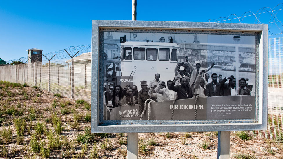 Poster showing prisoners freed from Robben Island, outside the prison itself