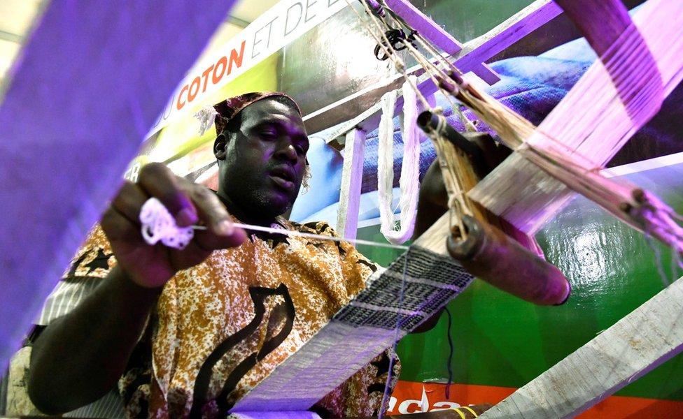 في مكان آخر من المدينة، يشتغل عامل النسيج على آلة النسيج...