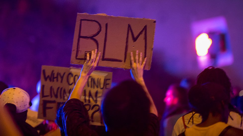 Persona sosteniendo un letrero que dice BLM, por Black Lives Matter