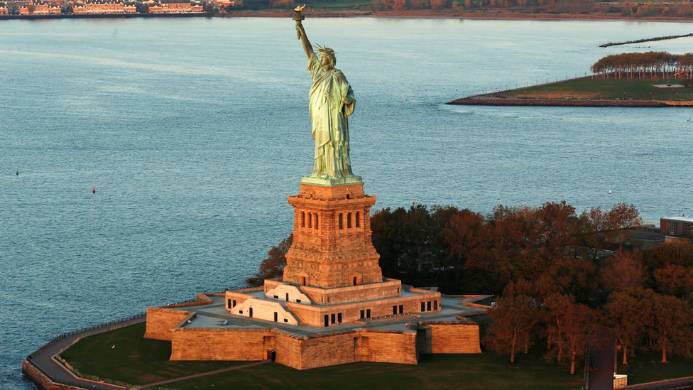 The sun lights the Statue of Liberty which is on the UNESCO World Heritage Cultural List in New York