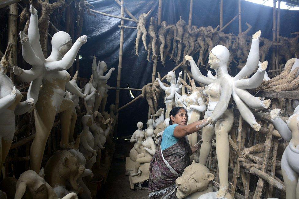 فنانة هندية تجهز تماثيل من الطين استعدادا لانطلاق مهرجان دورغا بوجا، حيث يحتفل الهندوس بهذه الإلهة التي تجسد القوة وانتصار الخير على الشر. ويستمر المهرجان خمسة أيام.