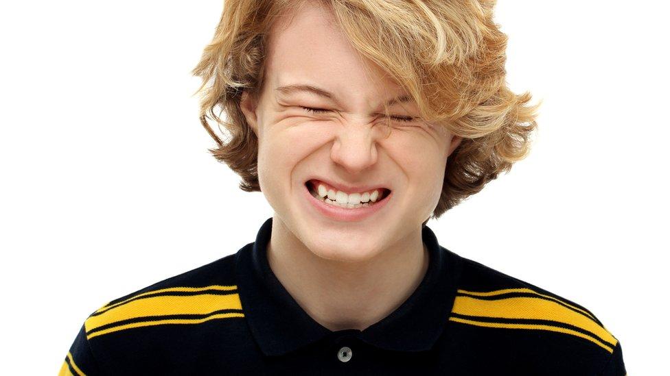 Adolescente apretando los dientes