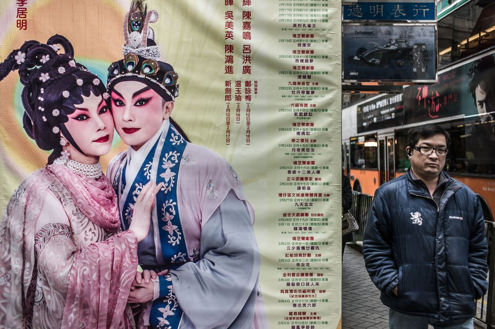 A man walks past a billboard advertising for the programme of a Cantonese Opera house in Hong Kong on January 15, 2013.