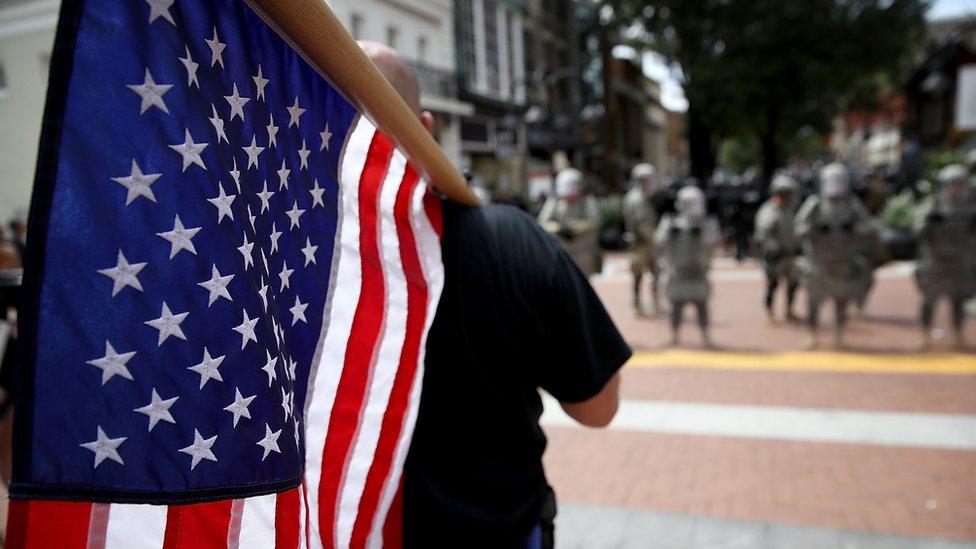 Un manifestante con la bandera de EE.UU. en Charlottesville.