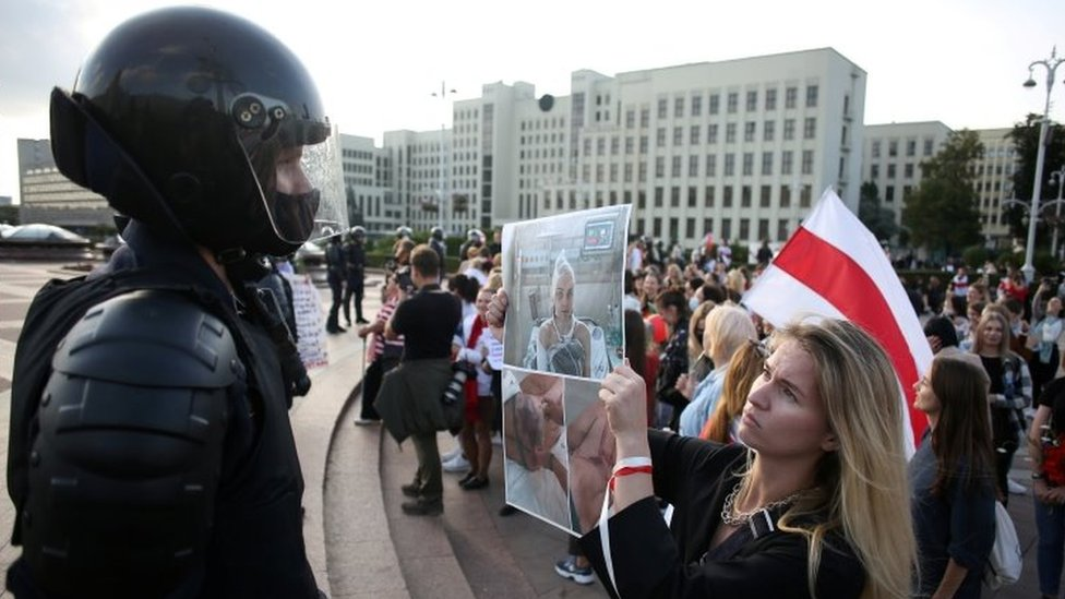 A woman holds pictures of protesters allegedly beaten by police in front of a riot police officer in Minsk, Belarus. Photo: 5 September 2020
