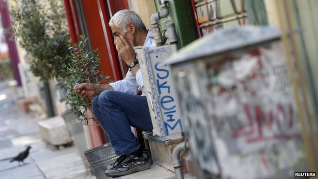 A vendor sits on the steps in front of his shop in central Athens