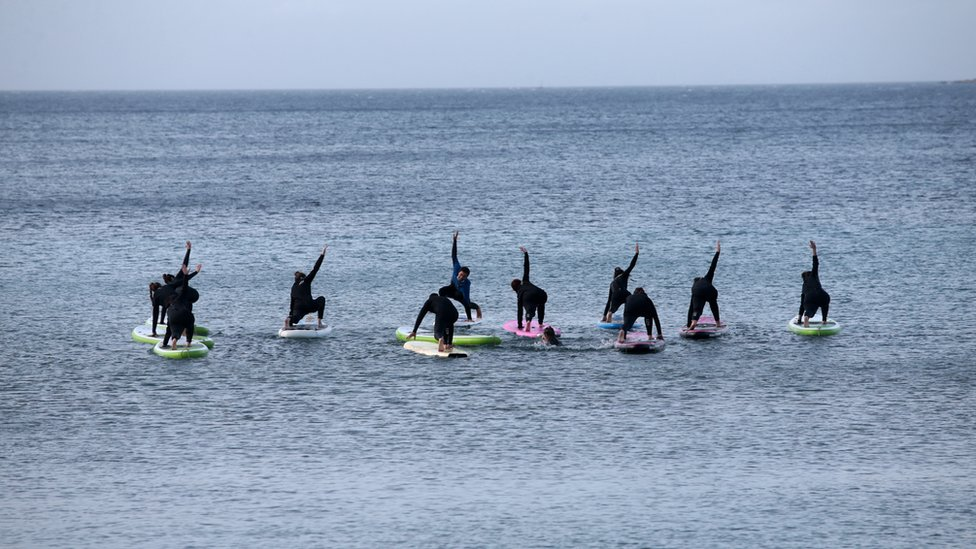 People exercise on paddle boards in the sea at a beach near Athens