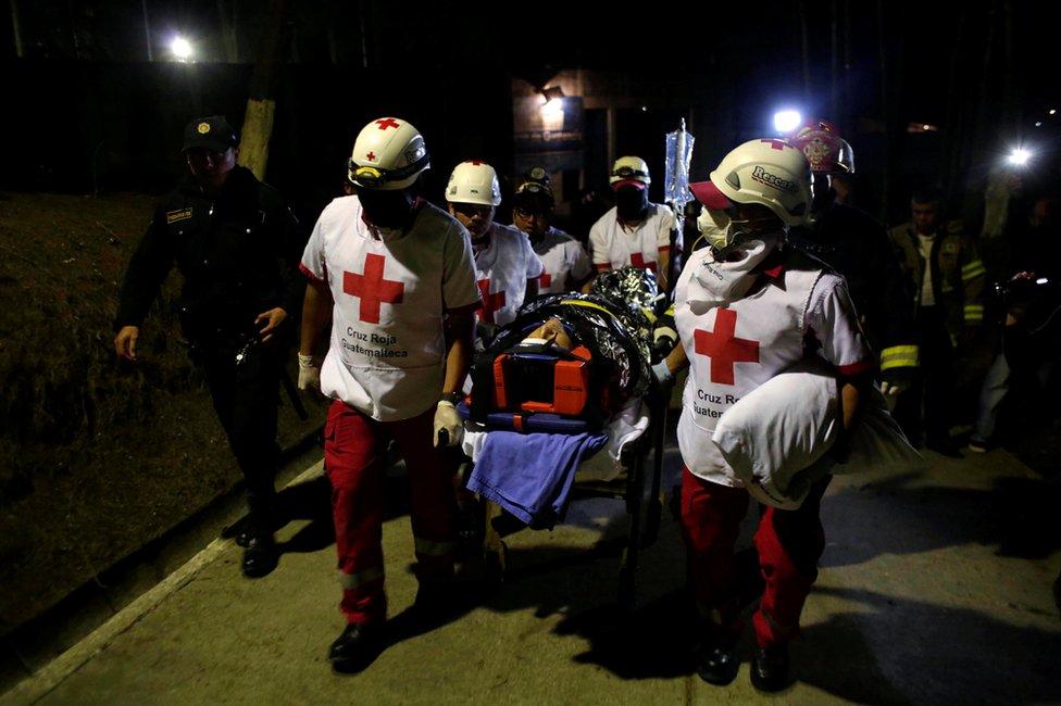 Voluntarios de la Cruz Roja trasladan a uno de los funcionarios heridos en el Centro Juvenil de Privación de Libertad para Varones Etapa II (Cejupliv) de Guatemala el 19 de marzo de 2017.