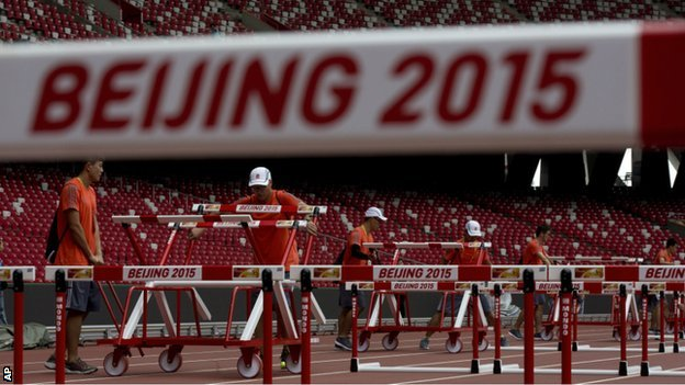 Volunteers put hurdles on the track at the Bird's Nest stadium in Beijing - 18 August 2015