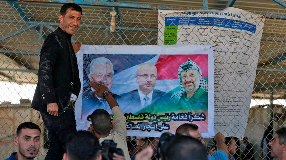 فلسطينيون يعلقون صور للرئيس عباس عند معبر إيريتس