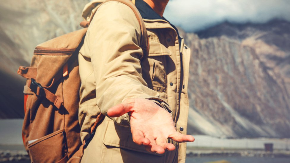 Un hombre tiende la mano en señal de ayuda.