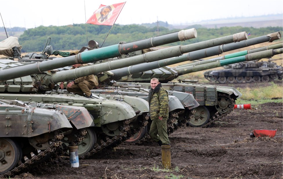 Pro-Russian separatists stand beside a tank in Donetsk