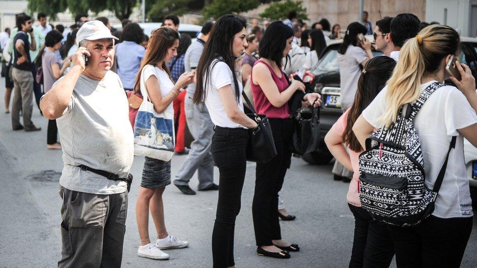 Gente de pie en una calle después de que le dijeran que evacuara sus edificios en Esmirna después de un terremoto de magnitud 6,3 que golpeó la costa del Egeo de Turquía occidental, el 12 de junio de 2017.