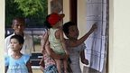 A woman with her childern checks the voters list at the Wahtheinkha village in Kawmhu township, Yangon, Myanmar