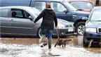 A woman walking through flood waters