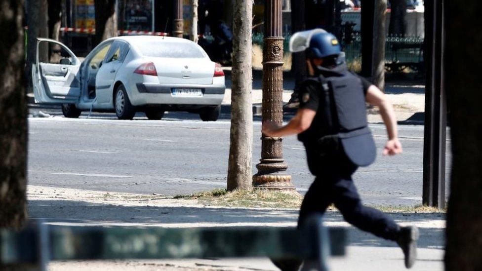 Un policía corre mientras de lejos se ve un auto con las puertas abiertas.