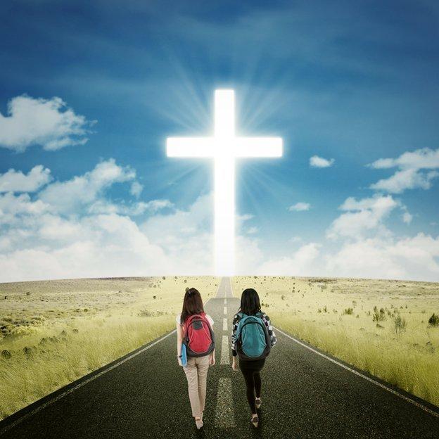 Dos niñas escolares caminando en dirección a la cruz cristiana
