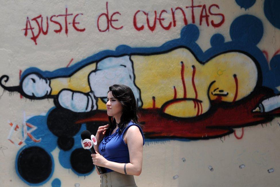 Periodista frente a un grafiti en el que se lee