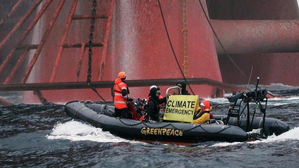 Greenpeace activists try to board oil rig at sea