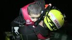 Rescue worker carries a young child