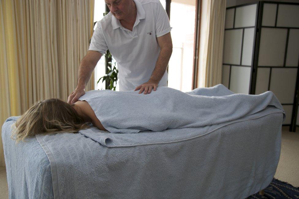 Colin Richards, terapeuta sexual de Intimacy Matters, da un masaje a una mujer tumbada en una camilla. (Foto: cortesía de Colin Richards/Intimacy Matters)