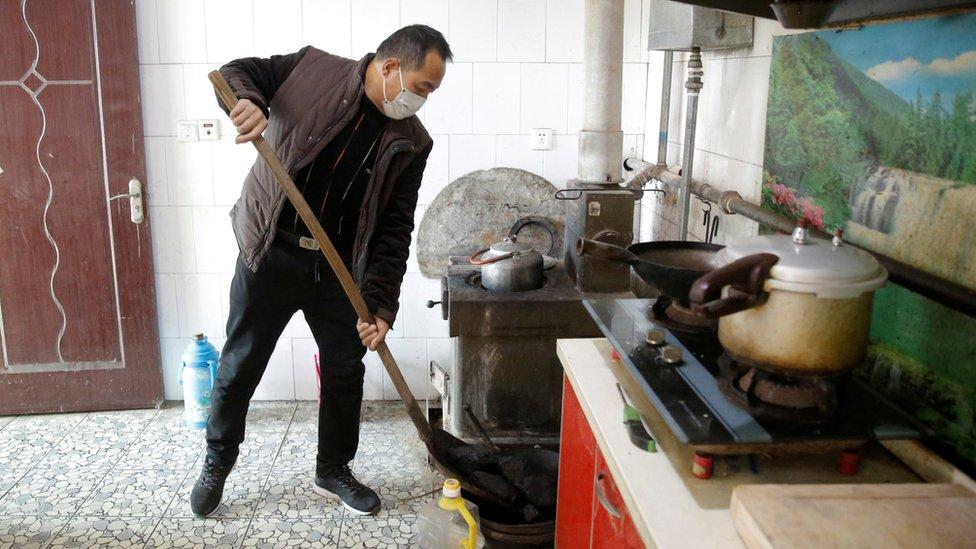 一名男子把煤放到用以取暖的煱爐裏