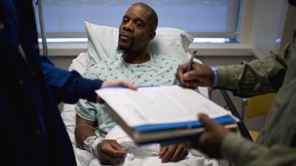 Un donante negro espera en una camilla que firmen una documentación antes de operarlo.
