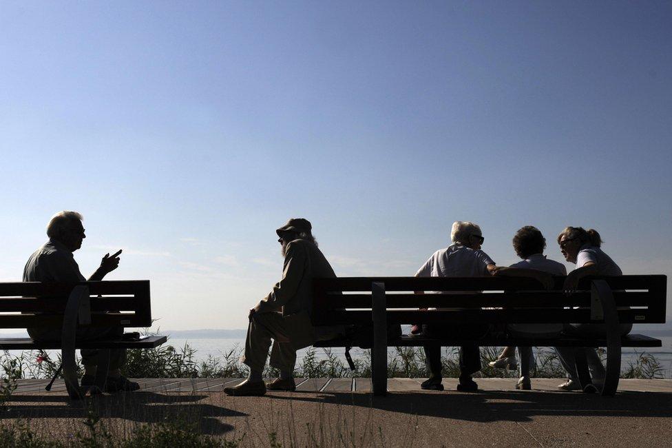 Ancianos sentados en dos bancos en Italia.